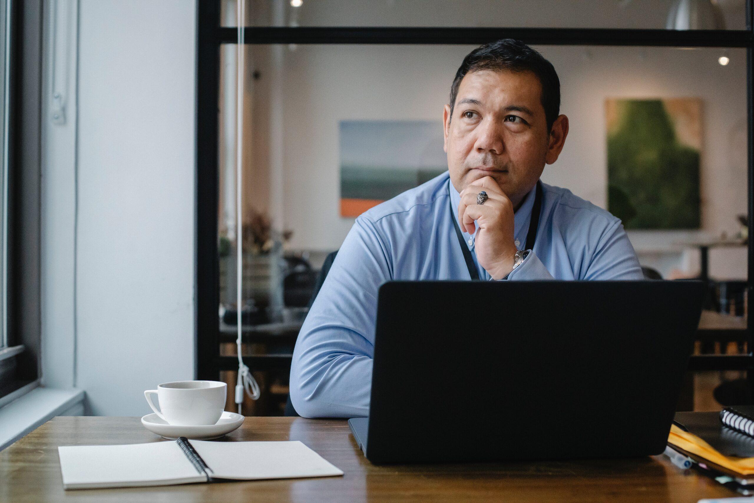 En ældre business mand sidder og arbejder på sit office kontor med sin computer og tænker